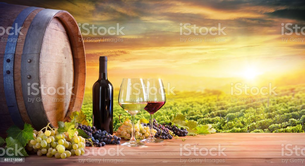 Wine Glasses And Bottle With Barrel In Vineyard At Sunset stock photo