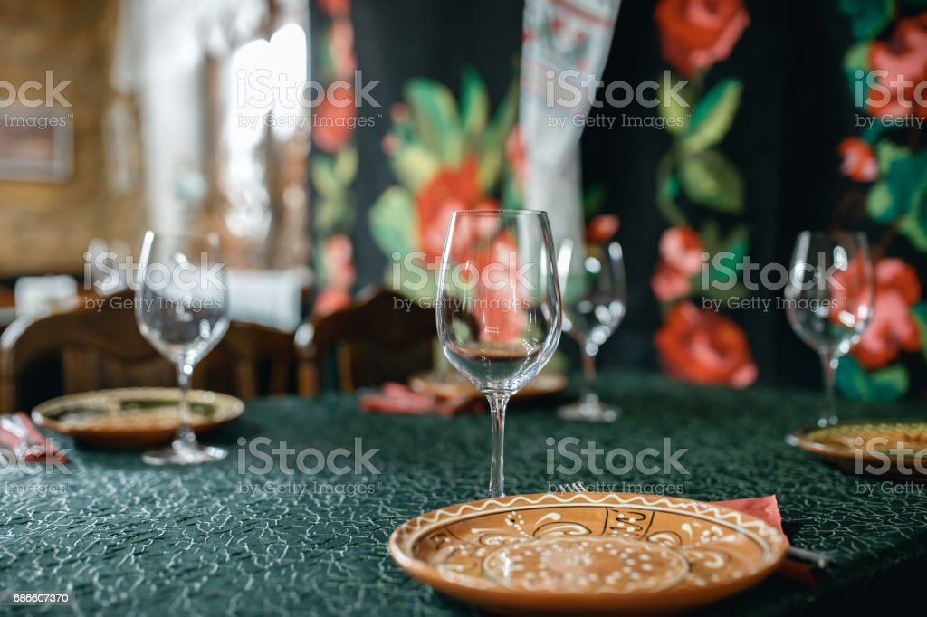 Wine glasses and table serving in rustic style restaurant royalty-free stock photo