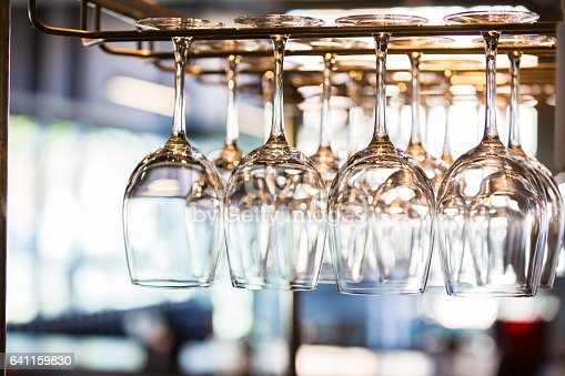 Clean wine glasses hang from rack at a restaurant or bar.