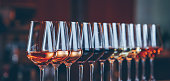 istock Wine glasses in a row. Buffet table celebration of wine tasting. Nightlife, celebration and entertainment concept 1084996508
