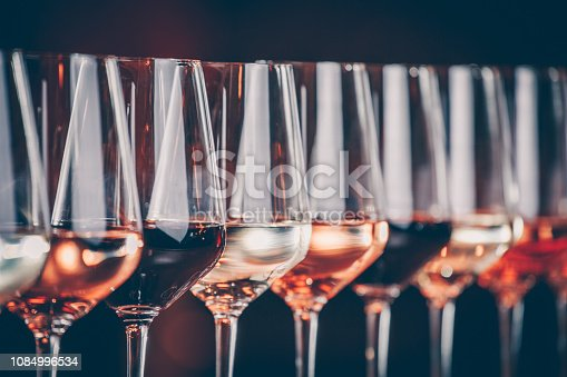 Wine glasses in a row. Buffet table celebration of wine tasting. Nightlife, celebration and entertainment concept. Horizontal, cold toned image