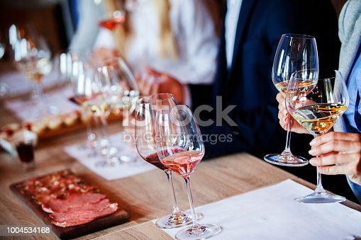 Adult people are sitting by the table. They were chosen like the best sommeliers in country. On this competition are presented best wines from wineries in region.Three glasses of white and red wine are in focus, showing bright color and transparency in crystal clear wine glasses.