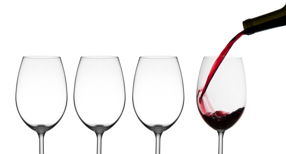 Red wine being poured into wine glasses and empty wine glasses Isolated on white background.