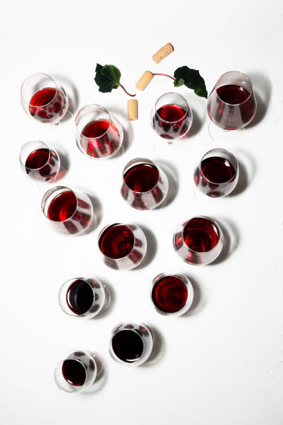Wine glasses placed forming a bunch of grapes with white background stock photo