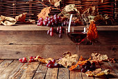 istock Wine, grapes and dried up vine leaves on a old wooden table. 1264009453