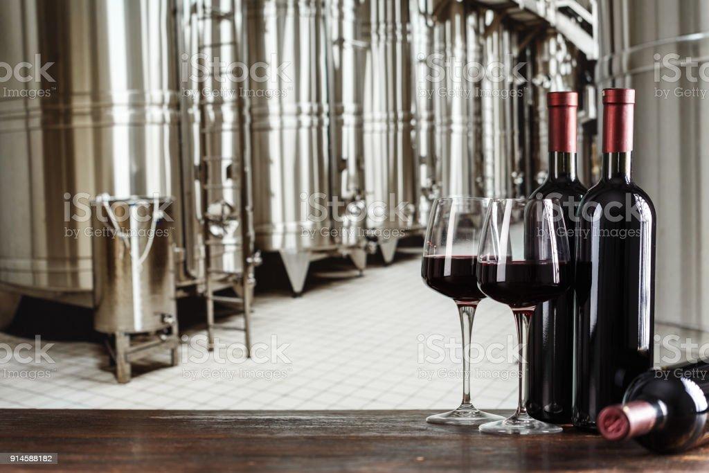 avec du vin à un producteur de vin dans des bouteilles sur le fond des citernes - Photo