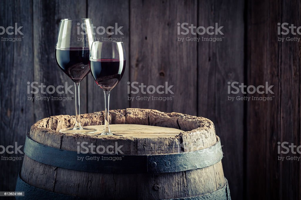 Wine in glass with grapes on old wooden barrel - foto stock