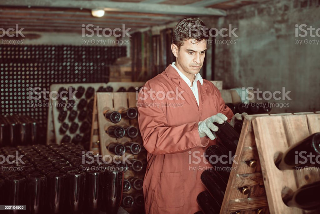 Wine maker taking care of seasoning bottles stock photo