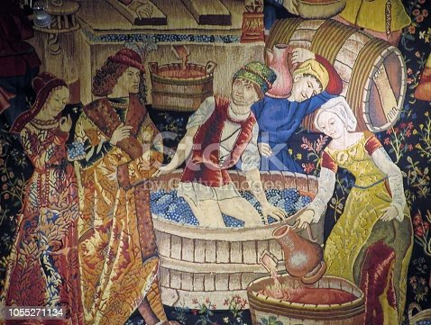 Wine making renaissance tapestry showing grapes being crushed in order to obtain wine.