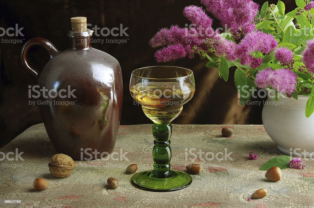 Wine, nuts and spiraea flowers in vintage style royalty-free stock photo