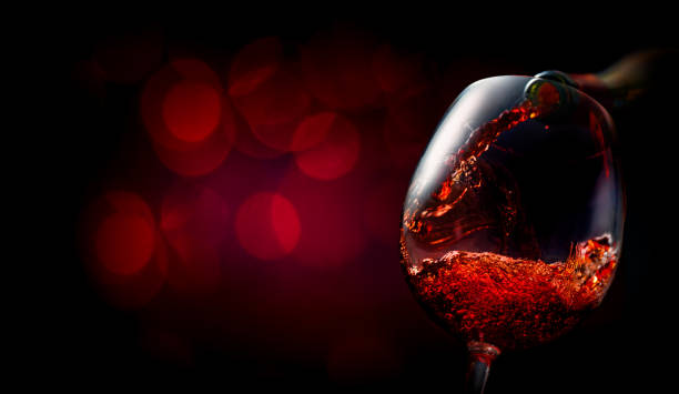 Wine on dark red Wine pouring into wineglass on dark red background red wine stock pictures, royalty-free photos & images