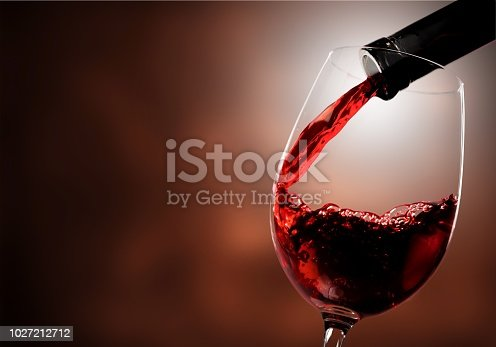Red wine pouring in glass on  background