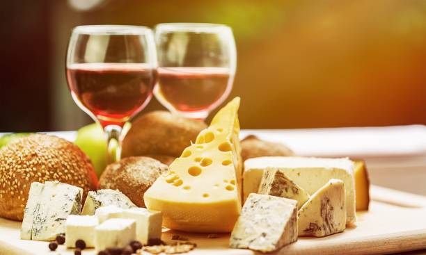 Wine. Assortment of cheese on board and two glasses of wine cheese stock pictures, royalty-free photos & images