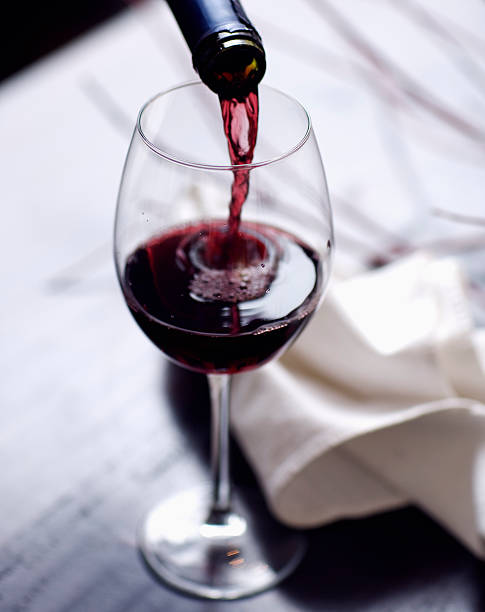 Wine Pour Elegant red wine pour in a fall setting with deep rich colors, twigs and napkin in the background. cabernet sauvignon grape stock pictures, royalty-free photos & images