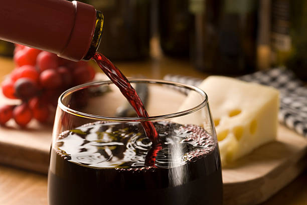 Wine pour with cheese and grapes wine pour. Cheese and grapes in the background merlot grape stock pictures, royalty-free photos & images