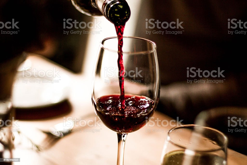 Wine Pouring into Glass stock photo