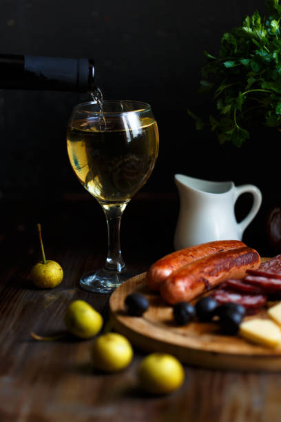 Wine pours into a glass goblet. On the table, meat appetizer, fried sausages, salami, cheese, olives. stock photo
