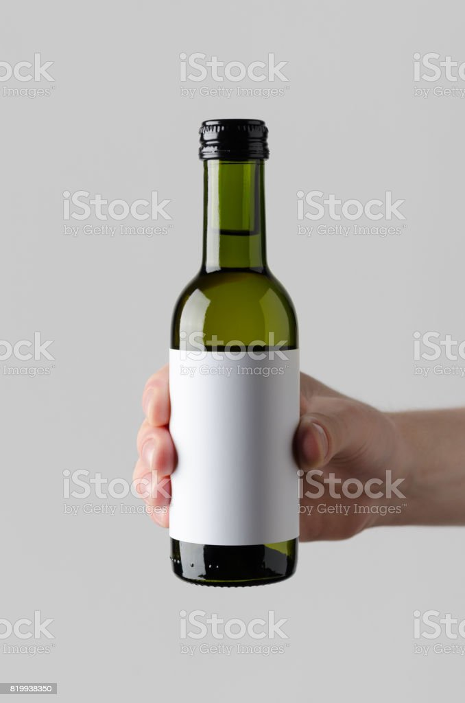 Wine Quarter / Mini Bottle Mock-Up. Blank Label - Male hands holding a wine bottle on a gray background stock photo