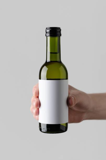 wein-viertel / mini flasche mock-up. leeres etikett - männliche hände halten eine flasche weine auf einem grauen hintergrund - mini weinflaschen stock-fotos und bilder