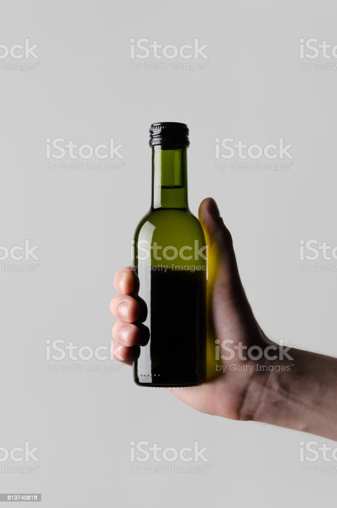 Wine Quarter / Mini Bottle Mock-Up - Male hands holding a wine bottle on a gray background stock photo