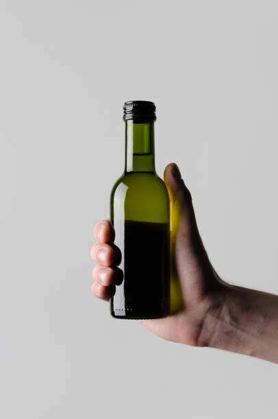wein-viertel / mini flasche mock-up - männliche hände hält eine flasche weine auf einem grauen hintergrund - mini weinflaschen stock-fotos und bilder