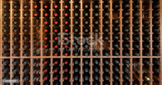 Wine rack with bottles for tasting at a winery. Useful background image, all maker's marks removed. Shot in ambient light.