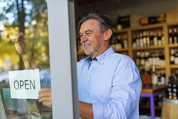wine shop owner holding open sign - petite entreprise photos et images de collection