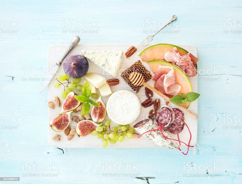 Wine snack set. Figs, grapes, nuts, cheese variety, meat appetizers and herbs stock photo