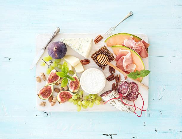 wein und snack-set. feigen, trauben, nüsse und käse-auswahl, fleisch appetithäppchen - salami vorspeise stock-fotos und bilder