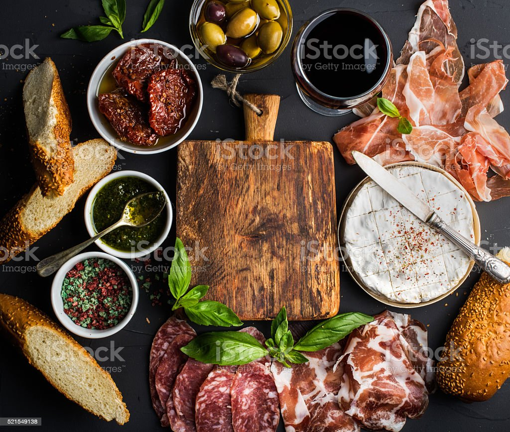 Wine snack set with empty wooden board in center. Glass stock photo