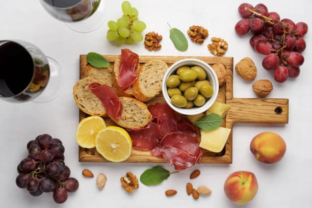 wine snacks on a cutting board. fresh bread, cold bresaol meat, lemon and parmesan cheese - bresaola foto e immagini stock