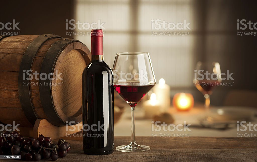 Wine tasting at restaurant Bottle, glass, grape and barrel still life with restaurant on background. Autumn Stock Photo