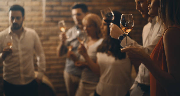 Wine tasting in a wine cellar. Closeup side veiw of group of adults during wine tasting in a wine cellar. There are three women and three men tasting different kinds of wines, selective focus. Low key. cellar stock pictures, royalty-free photos & images