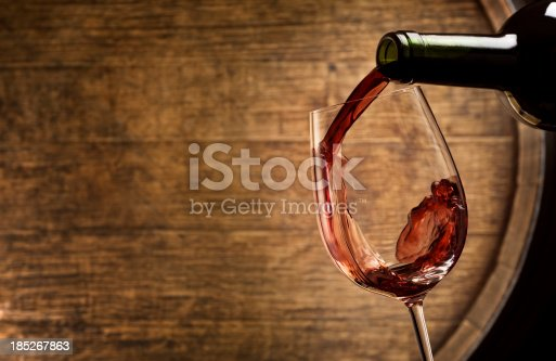 Close up of wine being poured with a wine barrel in the background.