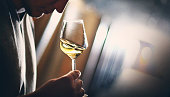 Closeup of unrecognizable adult man slightly shaking a glass of white wine under his nose and trying to catch bouquet. He's in wine cellar, there are blurry metal tanks in background. Backlit