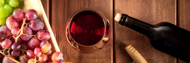 Wine Tasting Panorama. A red wine glass with a bottle, grapes, and a vintage corkscew, shot from the top on a dark rustic wooden background stock photo