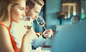 Closeup side view of two mid 30's adults tasting diferrent wine samples. They are holding wineglasses under their noses and smelling the wine while gently swirling the glasses to release the scent.