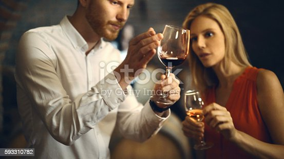 Closeup of mid 30's men and woman tasting different types of wine at a wine cellar. They are discussing its visual appearance, color as well as smell and taste. There are some blurry oak casks in background.