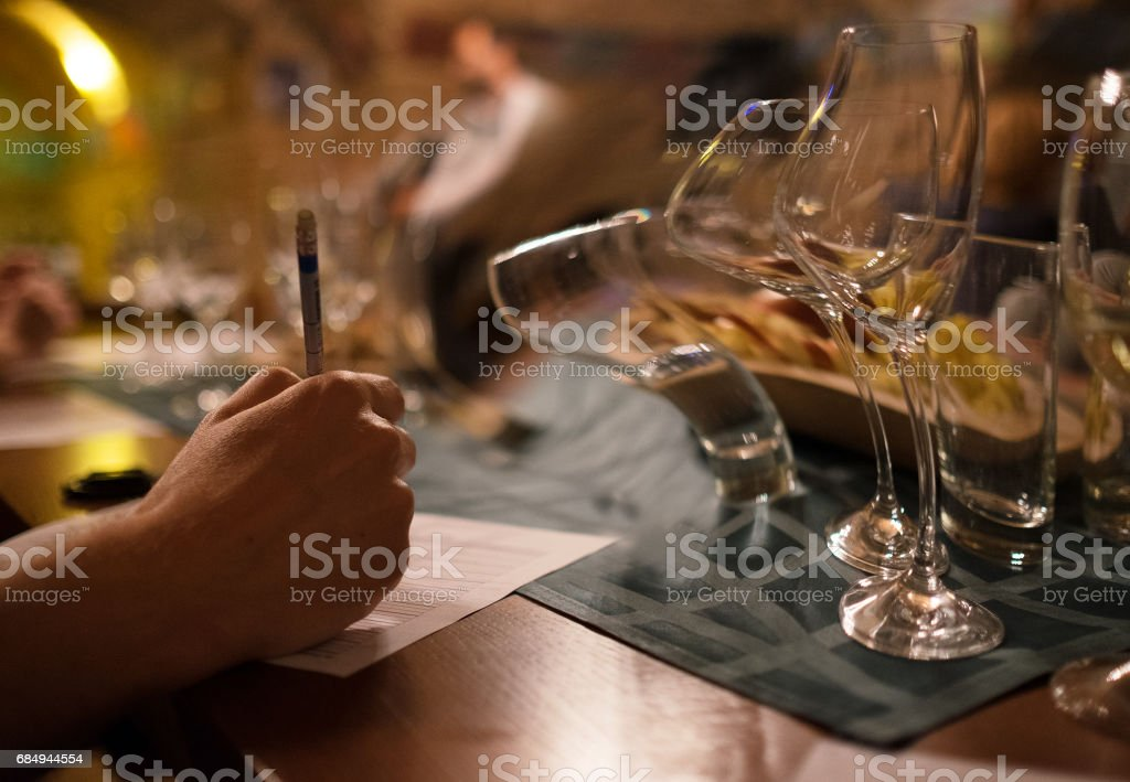 Wine tasting sommelier writes something after the 2 hours of testing Lizenzfreies stock-foto