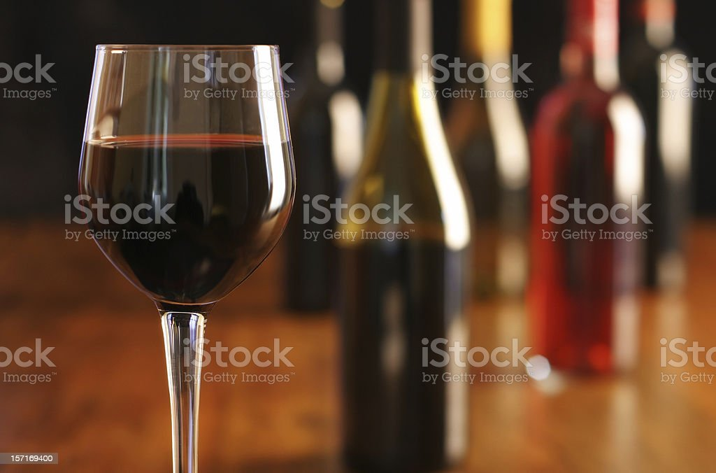 Wine Tasting with glass of red wine and multiple bottles royalty-free stock photo
