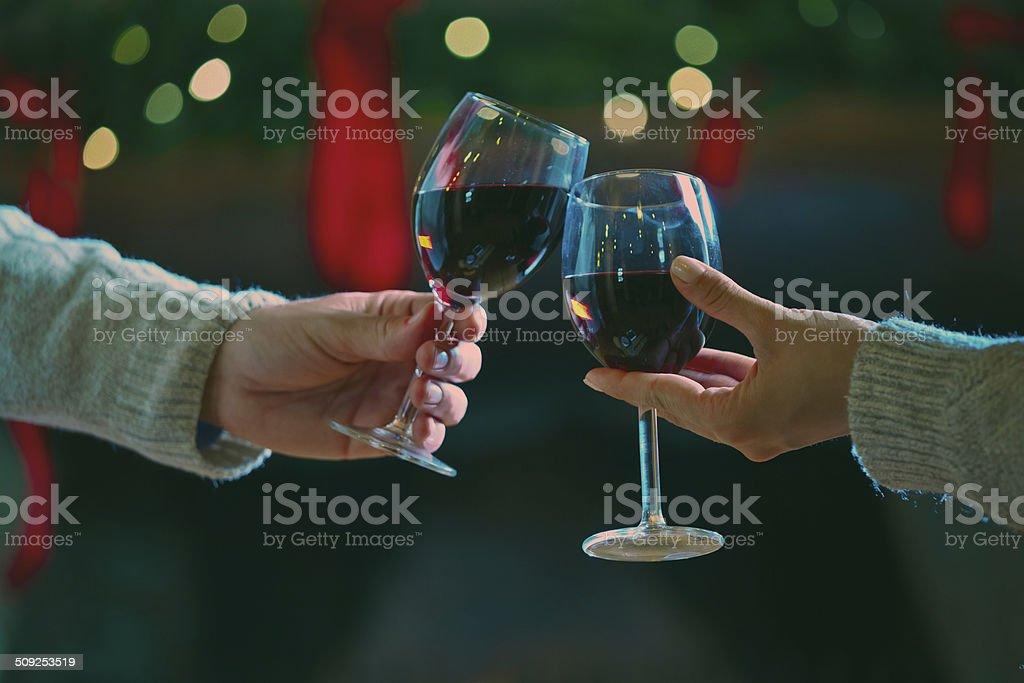 Wine toast Couple toasting with wine against christmas decoration. Focus on wine glasses. Adult Stock Photo