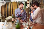 Heterosexual couple tasting white wine in the winery during degustation.