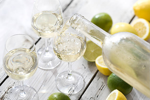 Wine with Citrus Flavour White wine being poured with citrus fruits to suggest flavour. white wine stock pictures, royalty-free photos & images