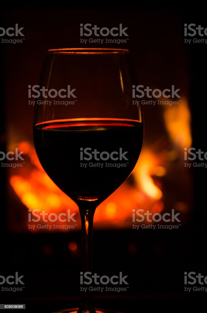 Wineglass by a cozy fire stock photo