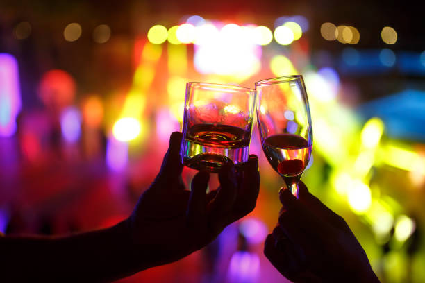 Wineglass of champagne in woman hand and a glass of whiskey in a man hand against a background of colored lights in a nightclub stock photo