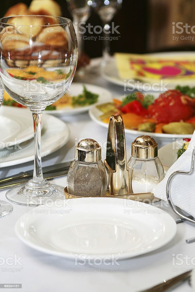 Wineglass, salt and pepper in restaurant royalty-free stock photo