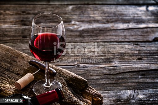 Wine bottle, wineglass with a corkscrew and a cork stopper shot on rustic textured wooden table. The composition is at the left of the table the table. Copy space available for text and/or logo. Predominant color is brown. Low key DSRL studio photo taken with Canon EOS 5D Mk II and Canon EF 100mm f/2.8L Macro IS USM.