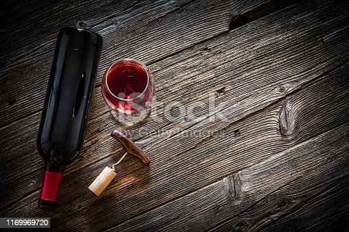 Top view of a wine bottle, wineglass with a corkscrew and a cork stopper shot on rustic textured wooden table. The wineglass is at the left of the table the table and the wine bottle is laying down beside  it. Copy space available for text and/or logo. Predominant color is brown. Low key DSRL studio photo taken with Canon EOS 5D Mk II and Canon EF 100mm f/2.8L Macro IS USM.
