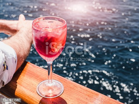 Beautiful wineglass with a pink cocktail and ice cubes, standing on the open deck against the backdrop of sea waves. Side view, close-up. Concept of leisure and travel