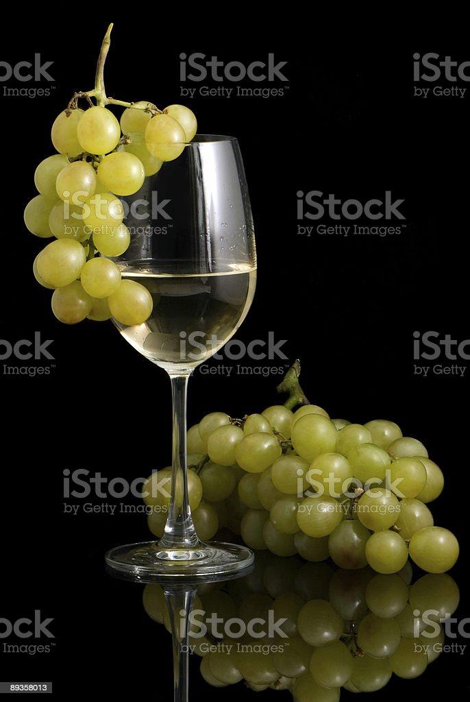 Bicchiere da vino bianco con vino e uva su sfondo nero foto stock royalty-free